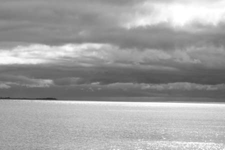 Water and sky with clouds on a stormy day looking afternoon overlooking a lake;  monochrome Stock Photo