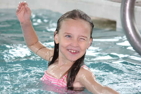 Young girl-child playing around, having fun in a swimming pool.