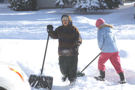 Ladies with shovels in the deep snow in the driveway after a big snow storm..