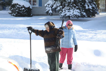 Ladies with shovels in the deep snow in the driveway after a big snow storm.
