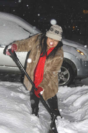 Lady with shovel, clearing deep snow,covering a sidewalk. Stock Photo