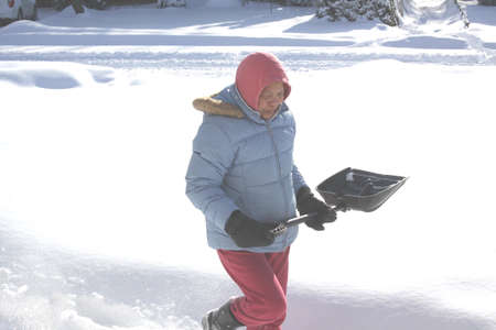 Lady with shovel in the deep snow covering a driveway