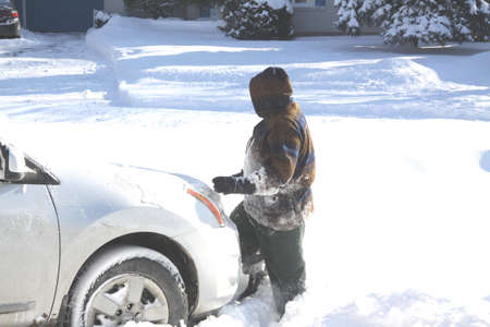 Lady in the deep snow cleaning off a car after a big snow storm Stock Photo