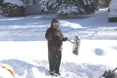 Lady in the deep snow, with shovel, clearing snow from driveway after a big snowstorm Stock Photo