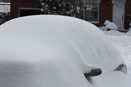 Snow completly covrering a small car in the driveway after a snow storm.