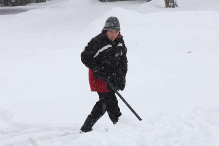 Lady shoveling snow during a heavy snow fall on an overcast afternoon. Stock Photo