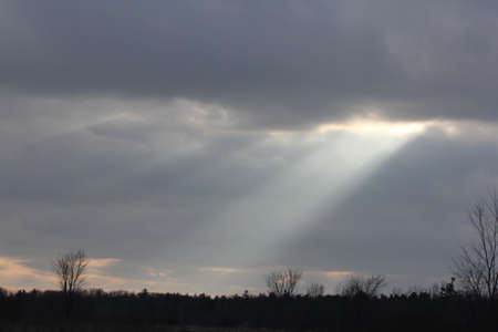 Sun rays streaming though clouds on a cloudy morning.