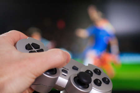 hand holding silver gamepad on a front of big screen with soccer game