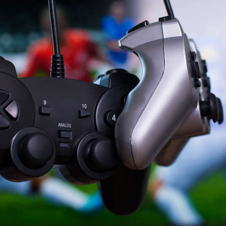 gamepads: black and silver gamepads close up with soccer game on background Stock Photo