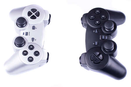 silver and black gamepads oposite each other isolated on a white