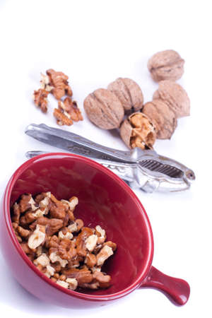 red plate with clean wallnuts and wallnuts with shell and nutcreacker near by on a white background photo
