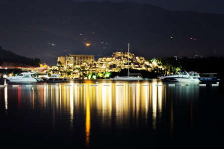 docks: night lights of little town close to the mountains view from a sea Stock Photo
