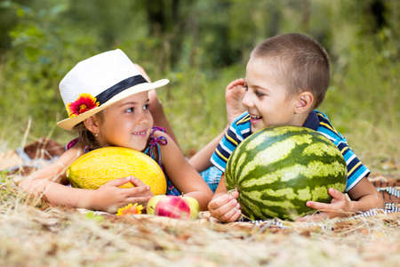 Happy smiling kids on a picnic with fruits looking to each other