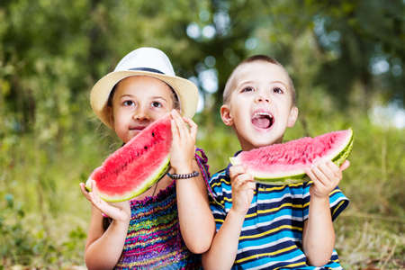 Happy smiling kids with watermelon on a picnic, close up
