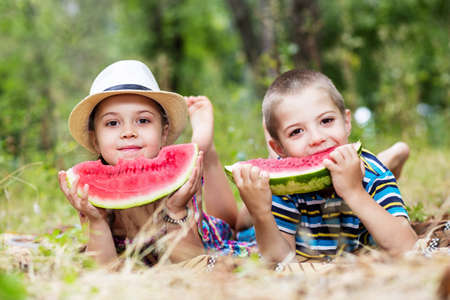 two happy kids on a park with red watermelon looking to the camera