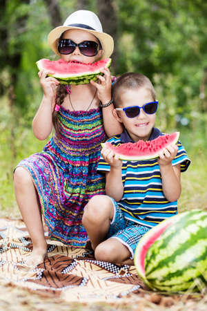 Kids at summer holidays. Sister and brother with watermelon and sunglasses.