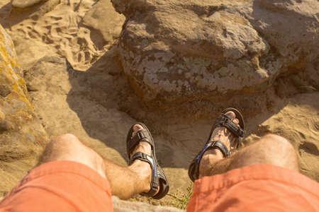 men's foots hangs down from a roc k on a desert