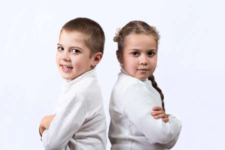 Cute brother and sister standing back to back, like they are in quarrel on a white background