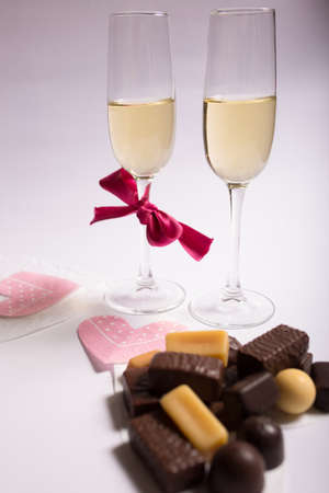 Two glasses of white wine with chocolates prepared for Valentine day