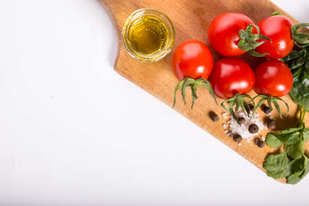 Cherry tomatoes with solt, spices olive oil on a kitchen board