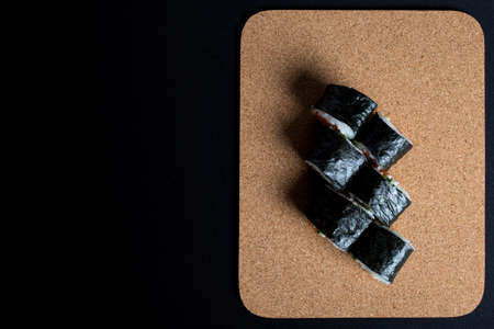 six rolls on wooden board on black background. Sushi with salmon on black background