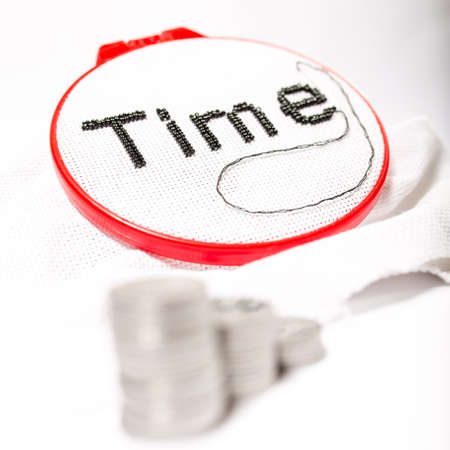 The word time is embroidered in black beads on a white background with a stack of coins on a white background.