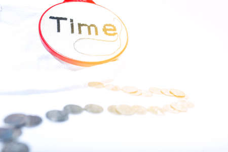 The word time is embroidered in black on a white background with a path of coins symbolizing payment