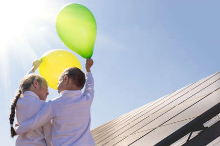 Children for saving the planet and using renewable energy sources. Happy kids with balls on the background of solar panels.