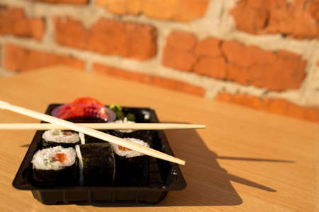 Sushi in a box in life style. Sushi to go on a table with brick wall on background.