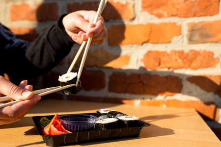 Hands picking with chopsticks one roll of sushi at home in lifestyle. Stock fotó