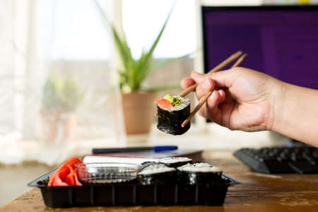 Order sushi for quarantine, at home. A hand takes chopsticks one roll from a box ordered for a house.