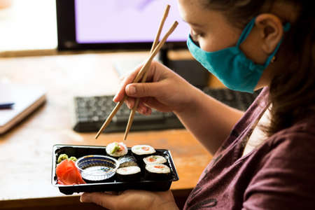 Young woman in a mask at home ordered a set of sushi online.