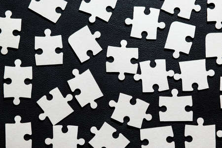 Large elements of white puzzles on a black background are evenly scattered. Puzzle and educational game for children