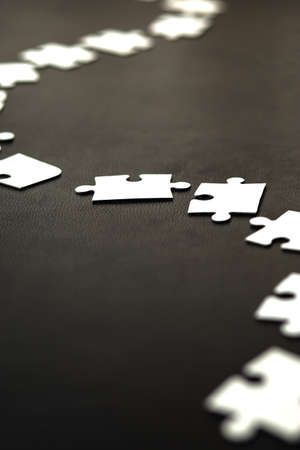 White puzzle elements laid out in a curved line on a black background.