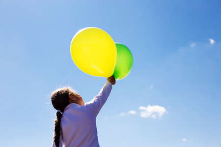 Girl with balloons on a background of clear blue sky. Children fight for pure nature
