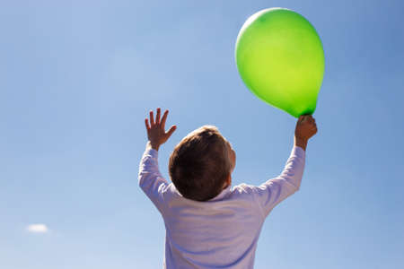 Little boy on a background of blue sky holds a green ball. Learning a new generation of love for nature.