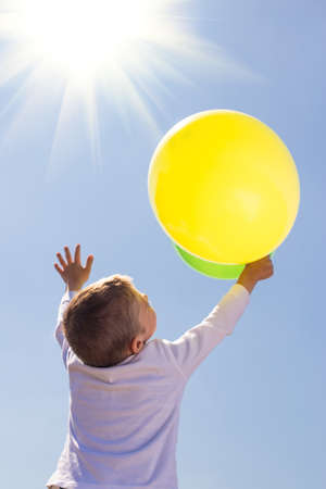 The boy holds balloons in his hands on a background of clear sky, raising his hands to the top