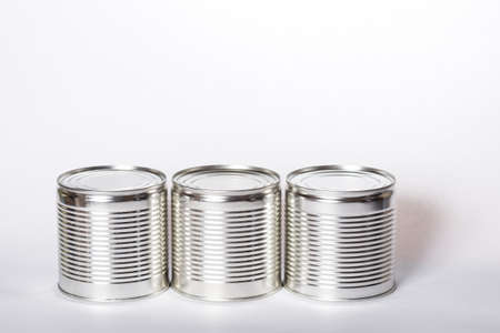 Three metal cans with preservation, with shadows on a white background. Cans with preservation with copyspace on white.