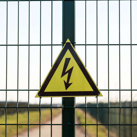 A warning sign about the danger of high voltage hardened in the fenced area of the power plant.