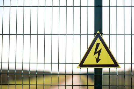 A warning sign about the danger of high voltage hardened in the fenced area, with copy space.