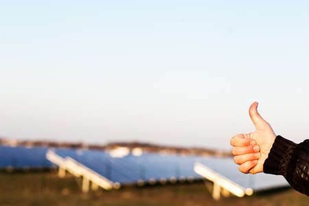 Thumb for renewable energy sources. Hand showing thumb with solar panels on background.