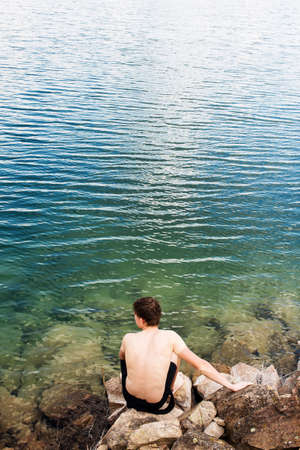 A man swims in the crystal clear water of a lake with a rocky shore