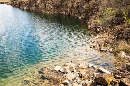 Rocky bank of the artificial lake with pure emerald water. Stock fotó