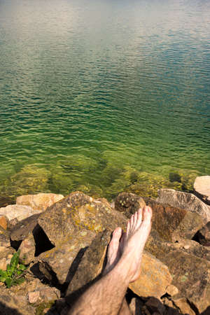 Lake with clean cold water and mans lags on a front