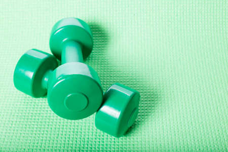 Green dumbbells on green fitnes mat with copy space.