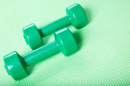 Green dumbbells on fitnes carpet with space for text