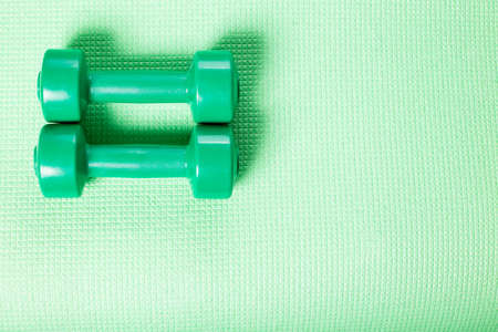 Green little dumbbells on green fitnes mat with copy space.
