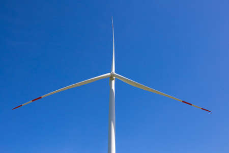 Wind generator against a blue sky in the middle of image.