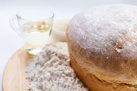 Just baked white wheat flour bread close up with ingredients.
