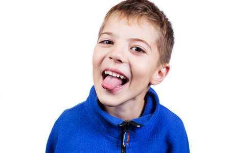 Portrait of difficult boy shows tongue isolated on a white.
